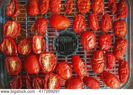 Tomatoes In The Vegetable Dryer. Dried Tomatoes On The Grill For Drying. Tomatoes Are Greased With O