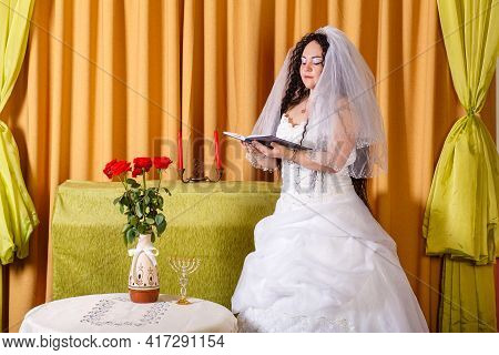 A Jewish Bride In A White Wedding Dress With A Veil Stands In The Hall At A Table With Flowers And P