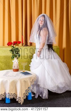 A Happy Jewish Bride In A Lush White Dress, Her Face Covered With A Veil, Stands In The Room Before
