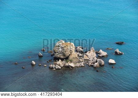 Group Of Rocks Without People In The Open Blue Sea. An Uninhabited Island.