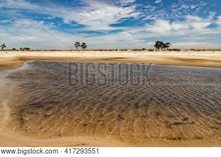 Sand, Clouds And Lake With Blue Sky