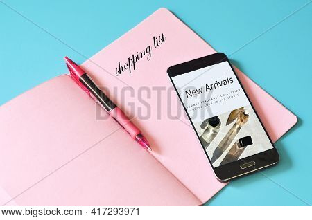 Shopping List In Pink Notebook, Online Shopping In Smartphone On Blue Background, Flat Lay.