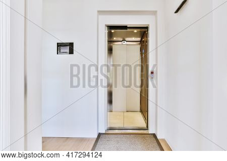 Elevator With Open Door In Light Hall With White Walls And Carpet In Modern Residential Building