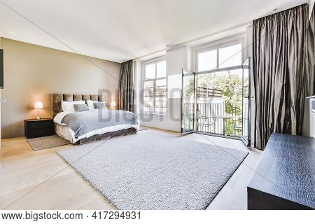 Comfortable Bed And Soft Carpet In Spacious Bedroom With Interior In Minimal Style