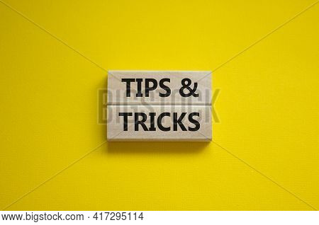 Tips And Tricks Symbol. Wooden Blocks With Words 'tips And Tricks'. Beautiful Yellow Background. Bus
