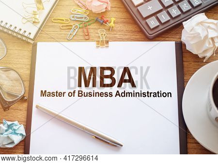 On A Wooden Table There Is An Office Sheet Of Paper With The Text Mba - Master Of Business Administr