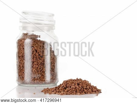 Fragrant Coffee Is Poured Into A Glass Jar. There Is A Pile Of Spilled Coffee Nearby.