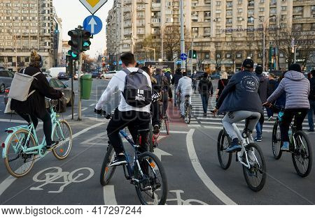 Bucharest, Romania - April 01, 2021: People On Bicycles Are Waiting To Cross The Street On The Bicyc