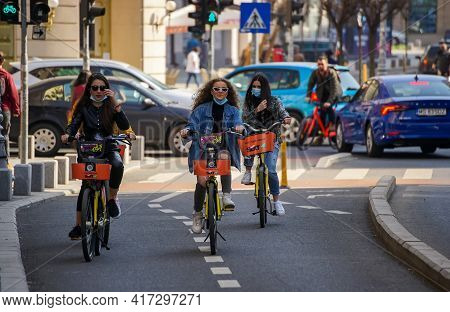 Bucharest, Romania - April 01, 2021: Three young women ride rented bicycles on the Victory Avenue bicycle track in Bucharest, Romania. This image is for editorial use only.
