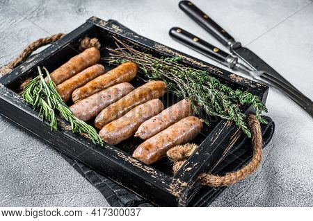 Roasted Bratwurst Hot Dog Sausages In A Wooden Tray With Herbs. White Background. Top View
