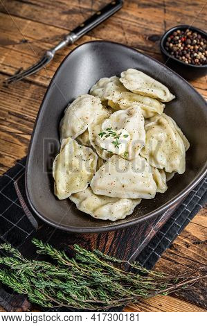 Dumplings Pierogi With Potato In A Plate With Herbs And Butter. Wooden Background. Top View