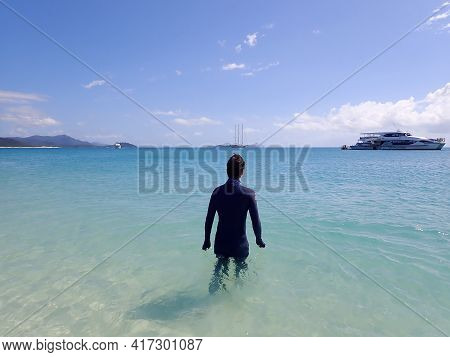 Whitehaven Beach, Whitsundays, Queensland, Australia - April 2021: Man Enters Clear Turquoise Water