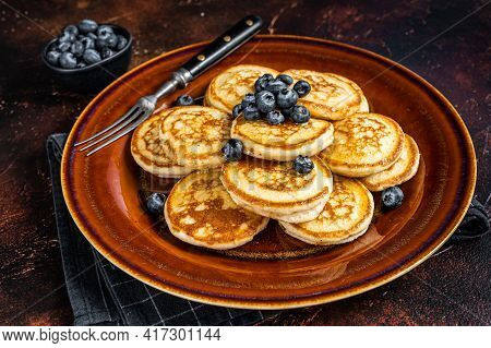 Plate With Pancakes With Fresh Blueberries And Syrup . Dark Background. Top View