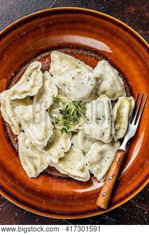 Polish Pierogi Dumplings With Potato In A Plate With Herbs And Butter. Dark Background. Top View