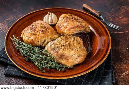 Roasted Chicken Thighs With In A Plate. Dark Background. Top View
