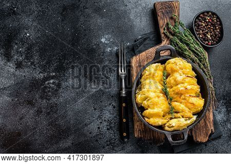 Potato Gratin Dauphinois In A Pan. Black Background. Top View. Copy Space