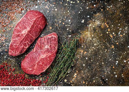 Raw Shoulder Top Blade Cuts, Beef Meat Steaks. Brown Background. Top View. Copy Space