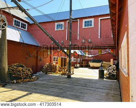 Red Wooden Fishery And Cannery Buildings With Boat, Fish Nets, And Buoys In Icy Strait Point, Alaska
