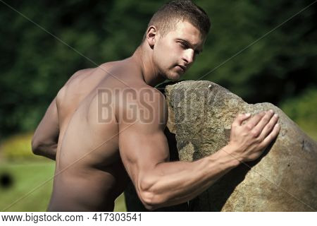 Man Bodybuilder With Muscular Torso, Biceps, Triceps Push Stone. Hard Work, Hardness, Strength Conce