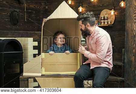 Father And Baby Son Concept. Little Cosmonaut Sit In Rocket Made Out Of Cardboard Box. Kid Happy Sit