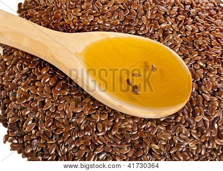 flax seed linseed and spoon oil closeup on white background