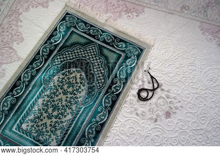 Close-up Green Prayer Rug And Rosary, Praying In The Month Of Ramadan