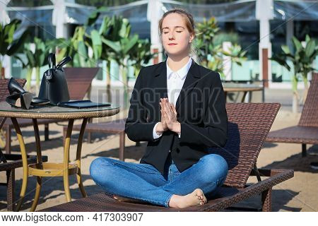 Young Beautiful Business Woman Or Freelancer Takes Coffee Break At Lounge And Demonstrates Meditatio