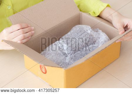 Closeup Hand Of Woman Opening Parcel Box With Check Product At Home, Female Unpack With Knife, Deliv