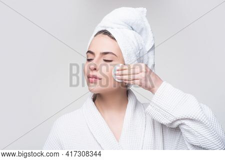 Closeup Of Beautiful Young Woman Washing Her Face With The Cotton Pad On The Gray Background. Eyes A