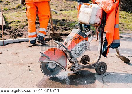 Orange Huge Tile, Concrete Or Asphalt Cut-off Saw Stand On The Ground During The Repair Works On The