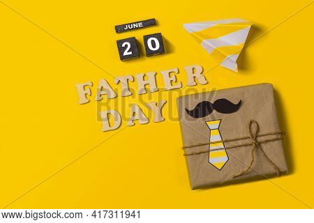 Gift Box On A Yellow Background With The Inscription In Wooden Letters Father's Day And The Date Of