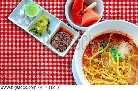 Northern Thai Curry Noodle Soup With Chicken And Side Dish In White Bowl On Red Checkered Tablecloth