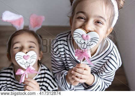 Funny Little Sisters With Easter Gingerbreads In The Form Of Bunny Faces And With Bunny Ears.
