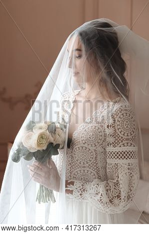 Young Bride In A Beautiful Boho Lace Dress Under A Long Veil. Wedding Photo Session, Bride's Morning