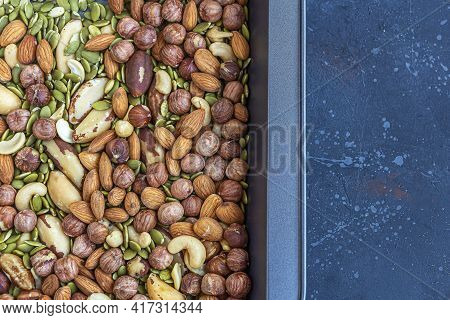 Various Types Of Nuts On Baking Sheet. Roast Cashew, Hazelnuts, Almonds And Brazil Nuts Close Up. He