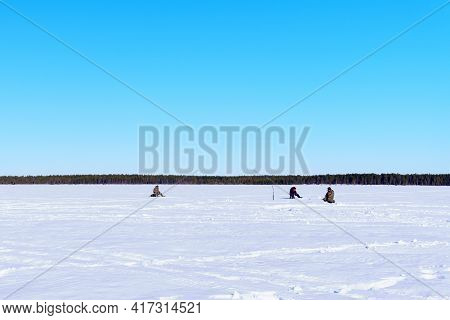 Fishermen Sit Fishing On A Winter Lake Against A Background Of Forest And Blue Sky. Sports Winter Fi