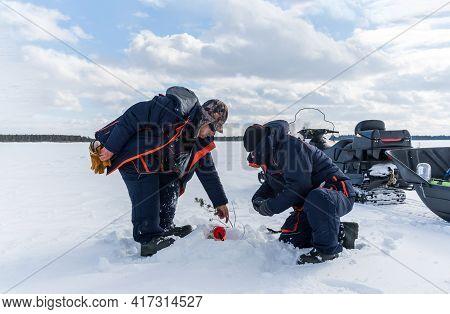 Fisherman Fishing On Frozen Lake. Snowmobiling, Winter Sports