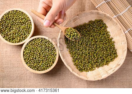 Mung Bean Seeds In Wooden Spoon Holding By Hand, Food Ingredients In Asian Cuisine And Produce Mung
