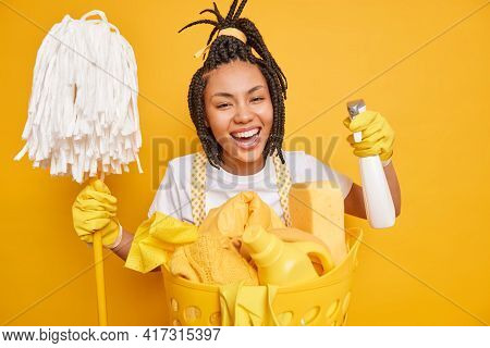 Smiling Positive Housewife With Dreadlocks Holds Mop And Cleaning Chemical Detergent Poses Near Laun