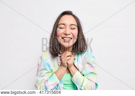 Grateful Positive Asian Woman Clasps Hands Has Beauty Face Smiles Toothily Keeps Eyes Closed Dressed