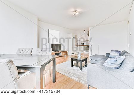 Contemporary Open Plan Kitchen With Dining Table Set And Gray Sofa In Light Spacious Room