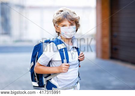 Happy Little Kid Boy With Medical Mask And Satchel Walk To School. Schoolkid On Way To School After