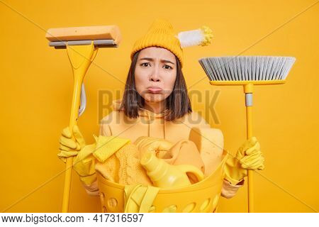 Unhappy Brunette Asian Woman Tired After Housecleaning Routine Holds Cleaning Tools Looks Sadly At C