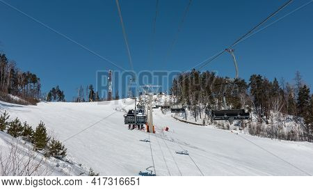 Chairlift Over A Snowy Mountain Slope. There Is A Forest On The Hills. Shadows In The Snow. Clear Bl