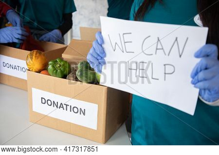 Focus On Vegetables, Volunteer Holding We Can Help Sign Board During Donations While Other Volunteer