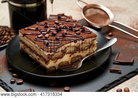 Portion Of Traditional Italian Tiramisu Dessert And Hand Coffee Grinder On Grey Concrete Background