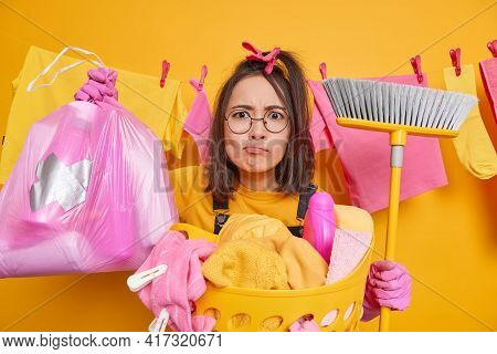 Serious Attentive Asian Woman Looks Puzzled Carries Trash Bag And Broom Does Laundry At Home Does Do