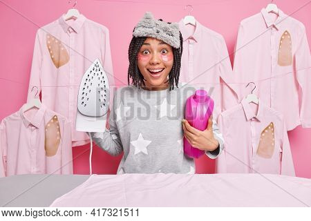 Happy Afro American Woman Smiles Broadly Holds Detergent And Electric Iron Dressed In Domestic Cloth