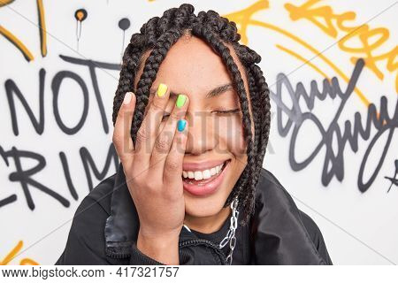Close Up Shot Of Happy Teenage Girl Makes Face Palm Smiles Broadly Has Colorful Manicure And Dreadlo