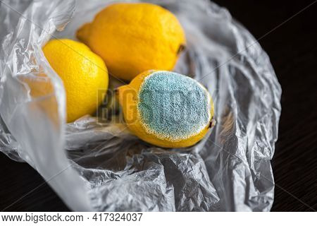 Three Whole Yellow Bright Lemons In A Cellophane Transparent Plastic Bag. One Lemon With Light Turqu